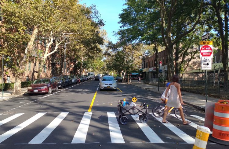 A woman crosses 39th Avenue on foot pulling a child in a wagon, while another child rides alongside her on a bicycle